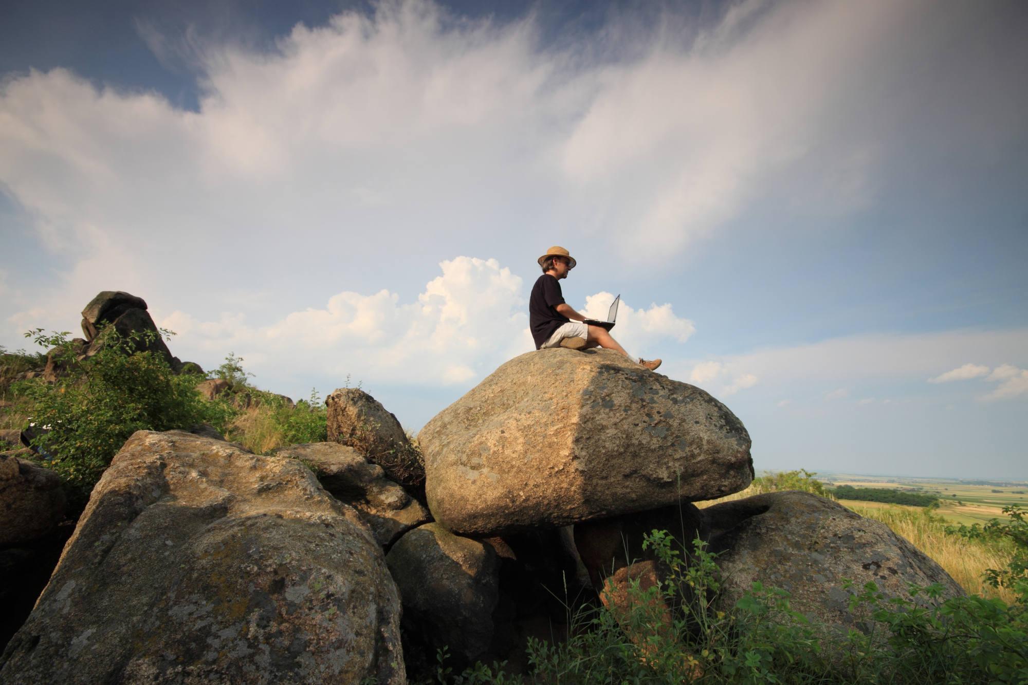 Mann sitzt mit Laptop in der Natur auf Steinen und über ihm der bewölkte Himmel