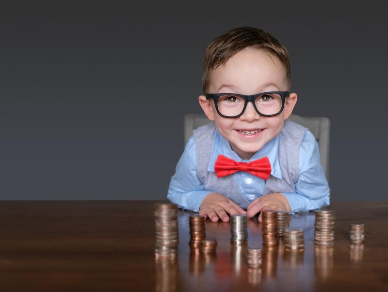 Junge mit Geld auf dem Schreibtisch